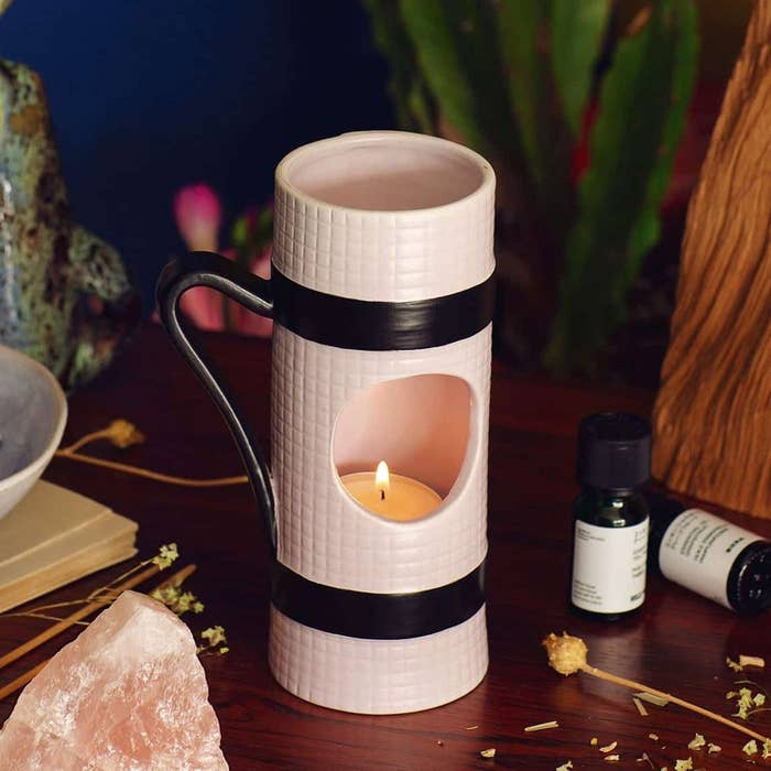 small tubular-shaped candle holder with hole in the middle, showing the candle inside made to look like a rolled-up yoga mat in white with black strap