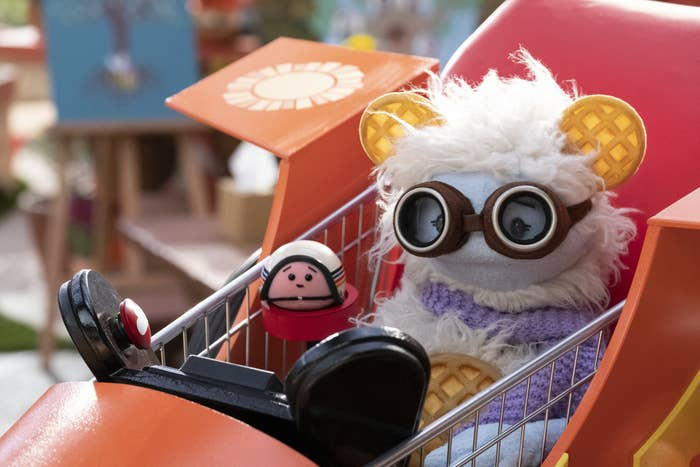 A furry puppet with frozen waffle ears, wearing protective flight goggles, is seated next to a round mochi puppet, wearing a helmet inside a flying go-kart