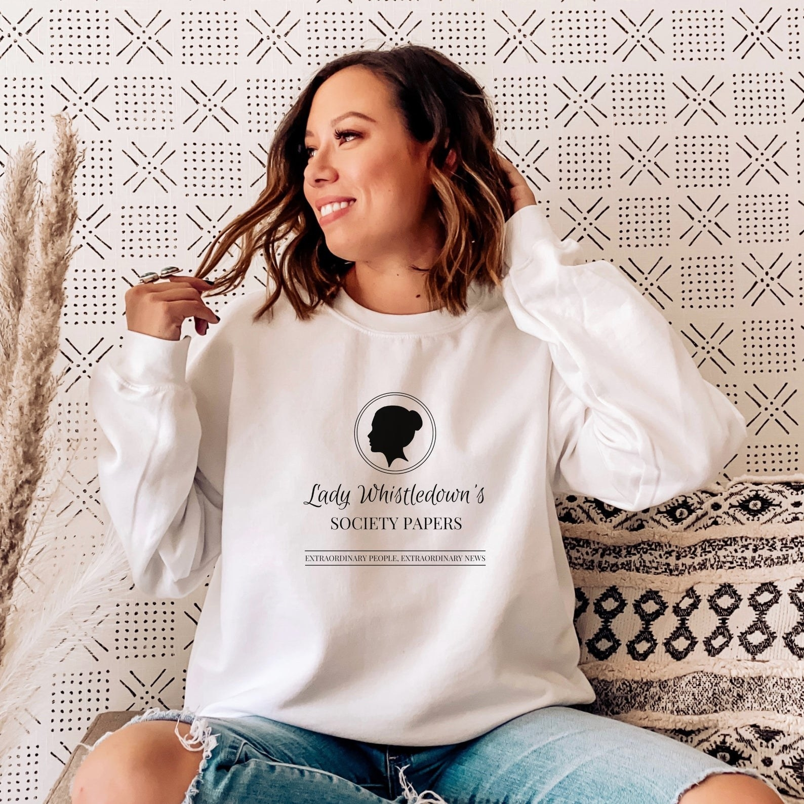 a model plays with their hair while wearing the lady whistledown's society papers sweatshirt in white