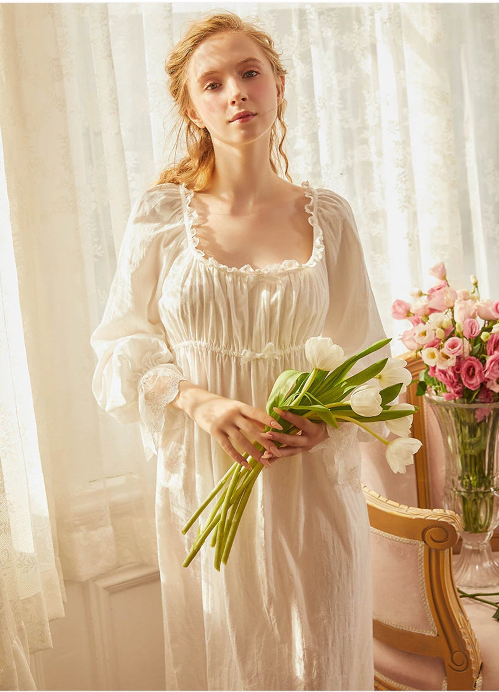 a model wearing the white victorian cotton square nightgown and holding a bouquet of tulips