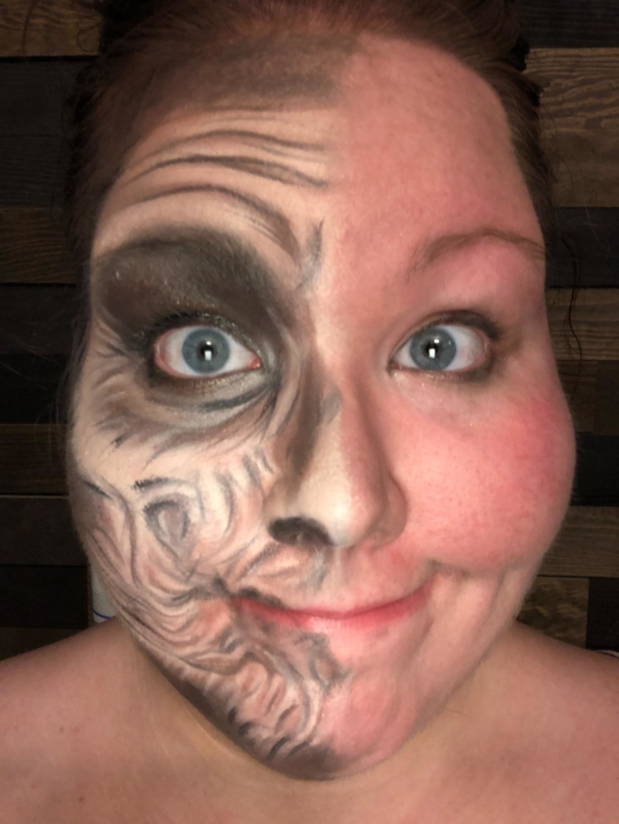 A reviewer wearing full-face Halloween makeup, with one side intact and the other side pretty much completely removed except for mascara