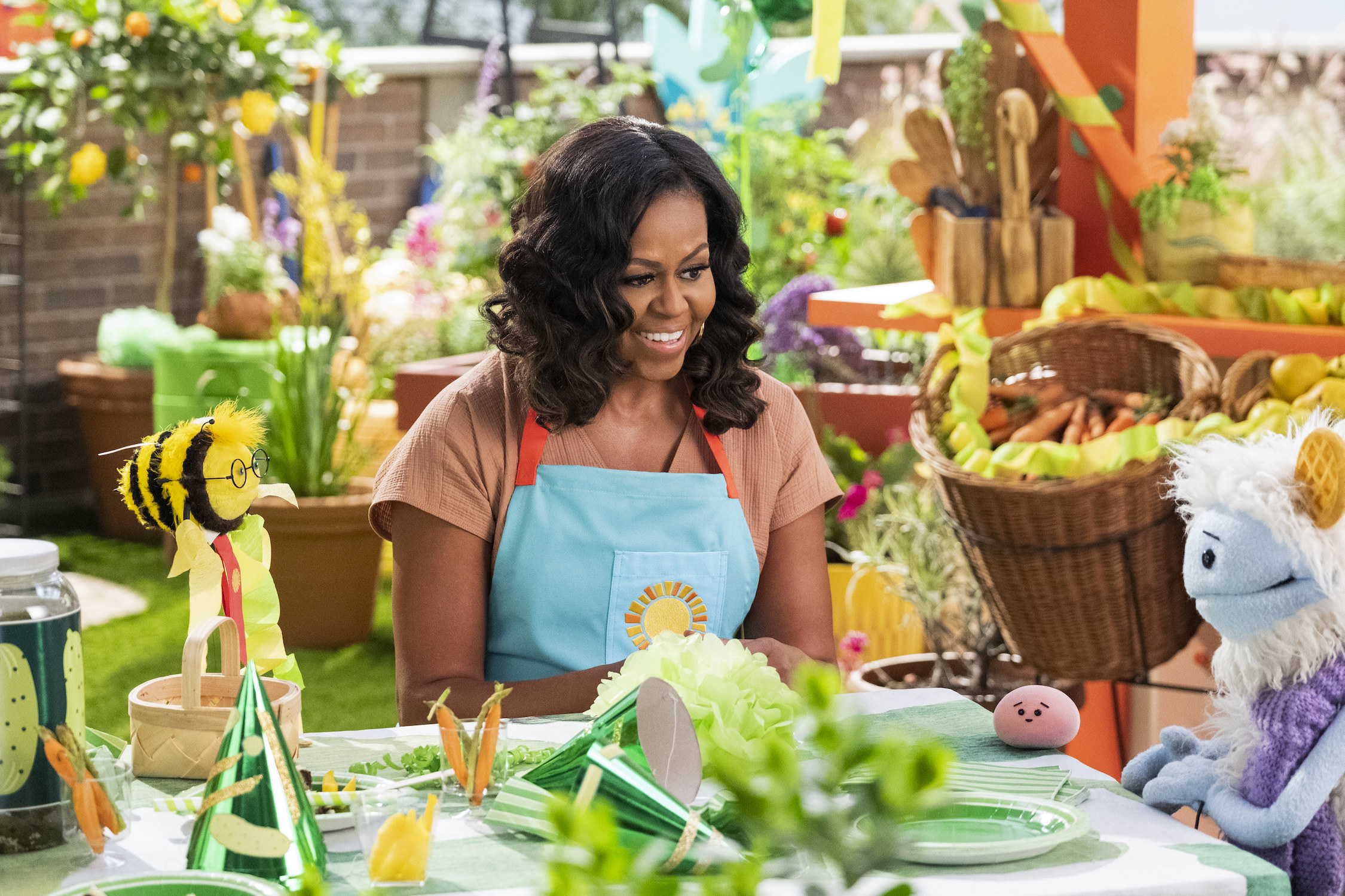 On a rooftop garden, Michelle Obama, wearing an apron, talks to Waffles, Mochi, and a bee puppet wearing a tie around a table dressed with decorations for a birthday party