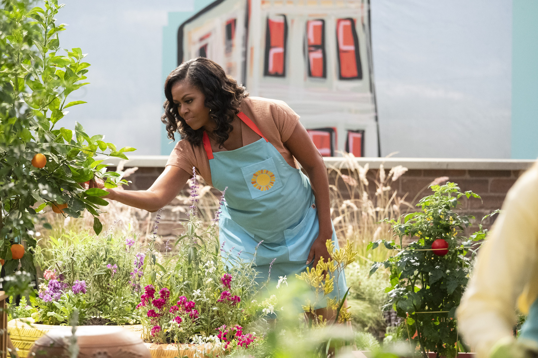 Michelle Obama looks at a plant in a rooftop garden