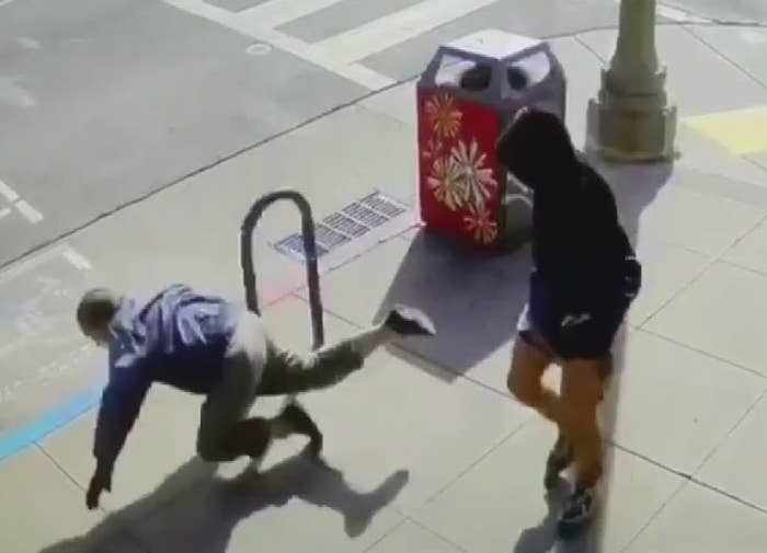 Screenshot of security footage shows someone falling on the sidewalk as the person who pushed them looks on