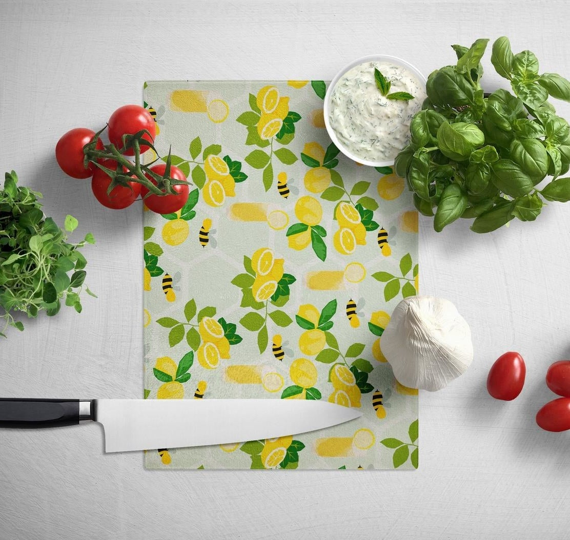 rectangle cutting board with illustrations of lemons and bees all over it