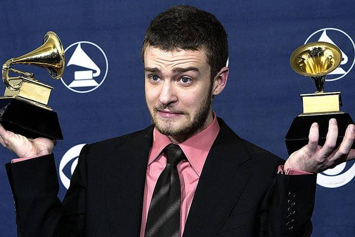Justin Timberlake holding up his two Grammy awards