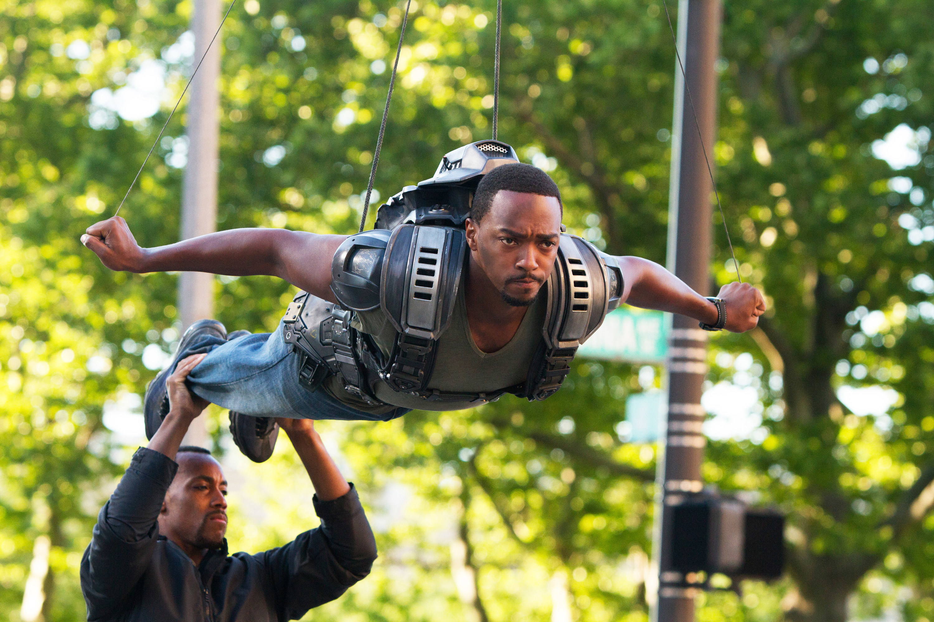 Anthony Mackie being held up by wire and pretending to fly as a man holds up his feet