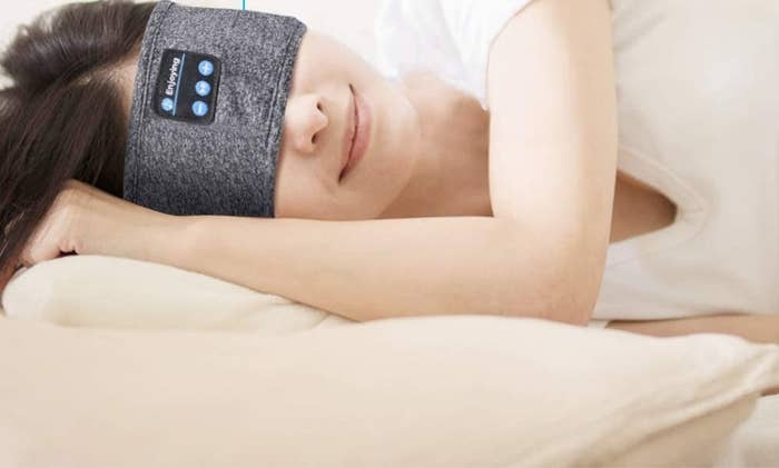 A person lying on their side while wearing the headband over their eyes