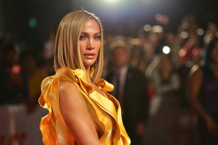 "Jennifer Lopez attends the ""Hustlers"" premiere during the 2019 Toronto International Film Festival in a gold dress"