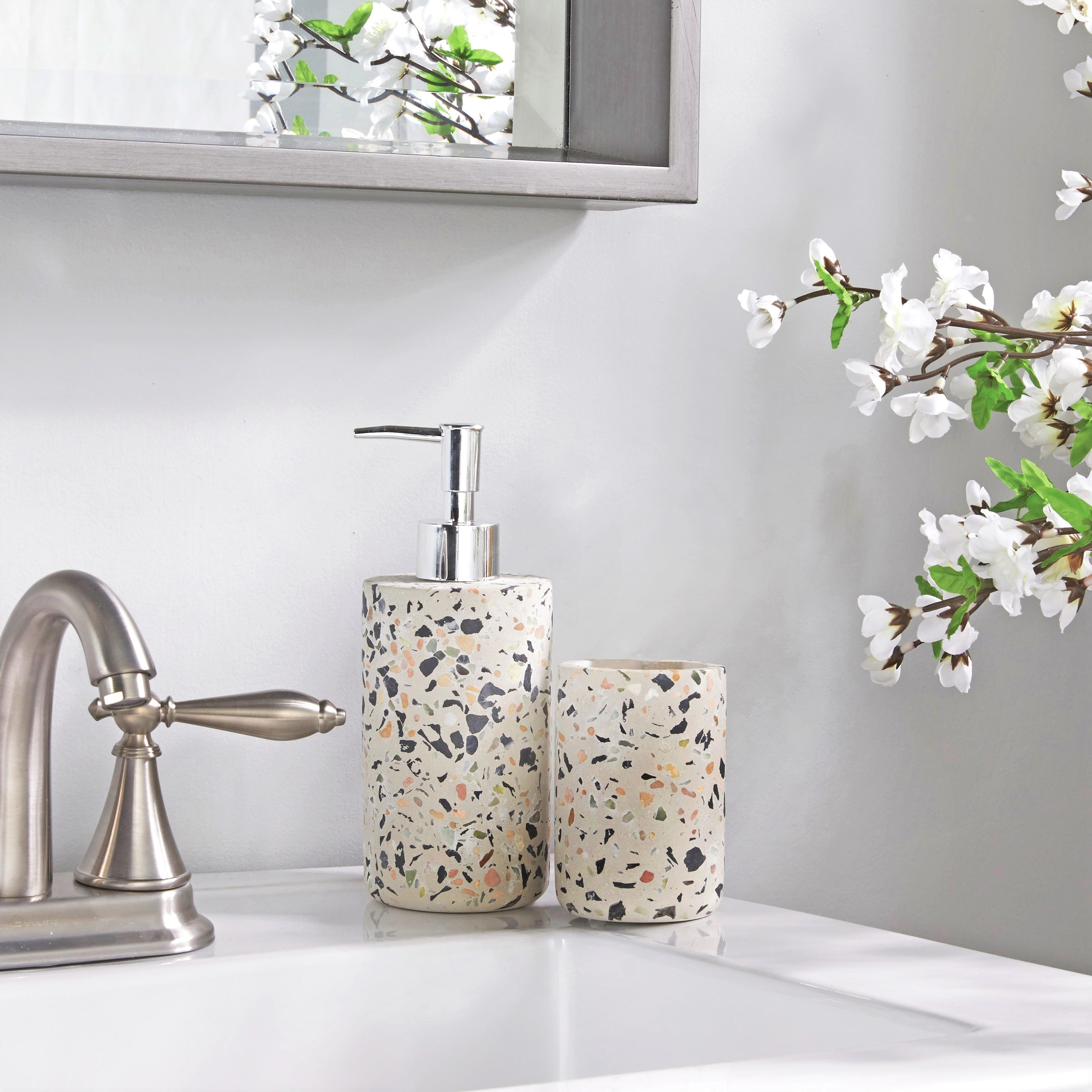 A white hand soap pump and a toothbrush cup in a terrazzo pattern