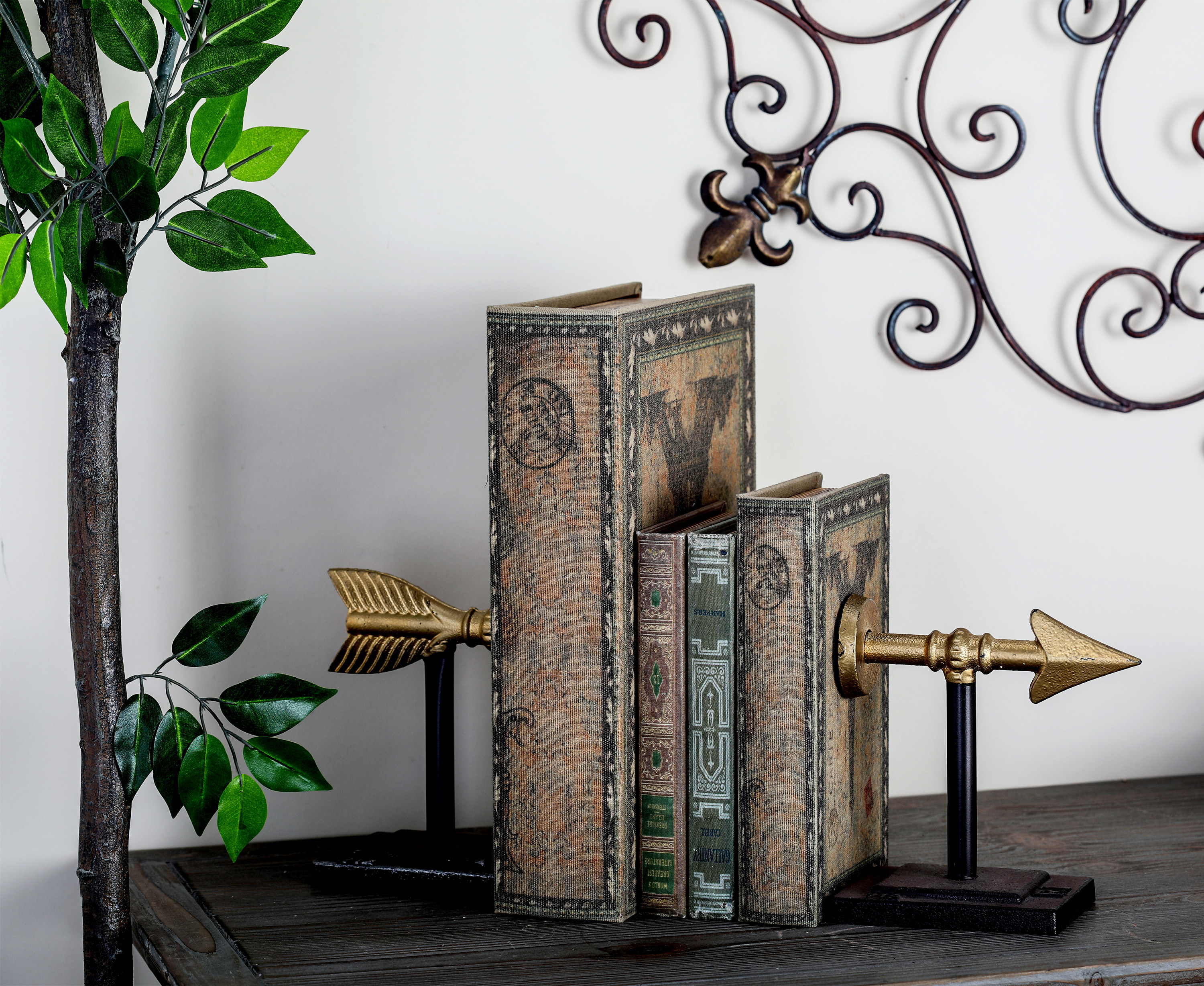 Two gold and black bookends that look like an arrow shooting through the books