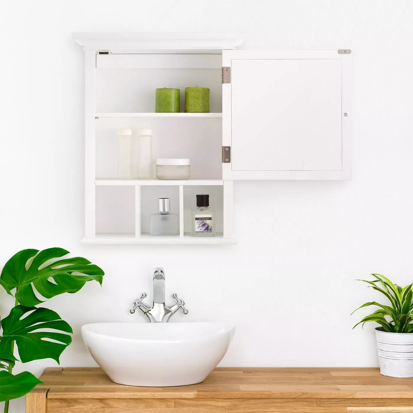 The open cabinet with internal shelves as well as shelves and a mirror on the outside