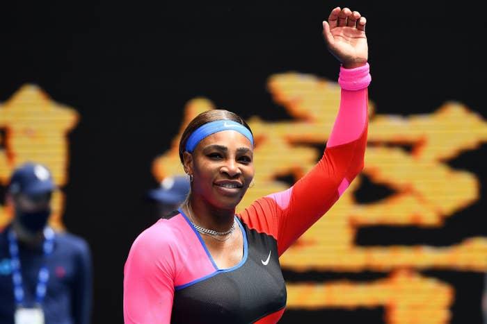 Serena Williams raises her arm in the air.