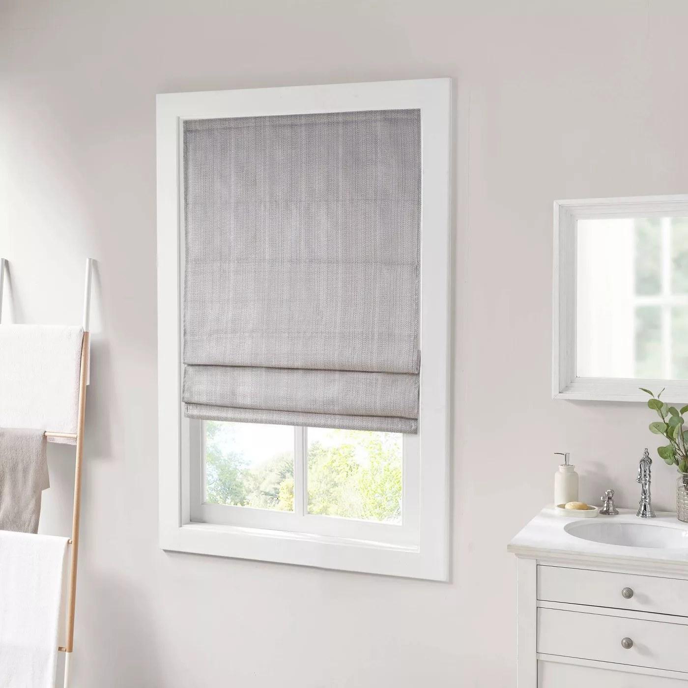 The Roman shade covering a bathroom window