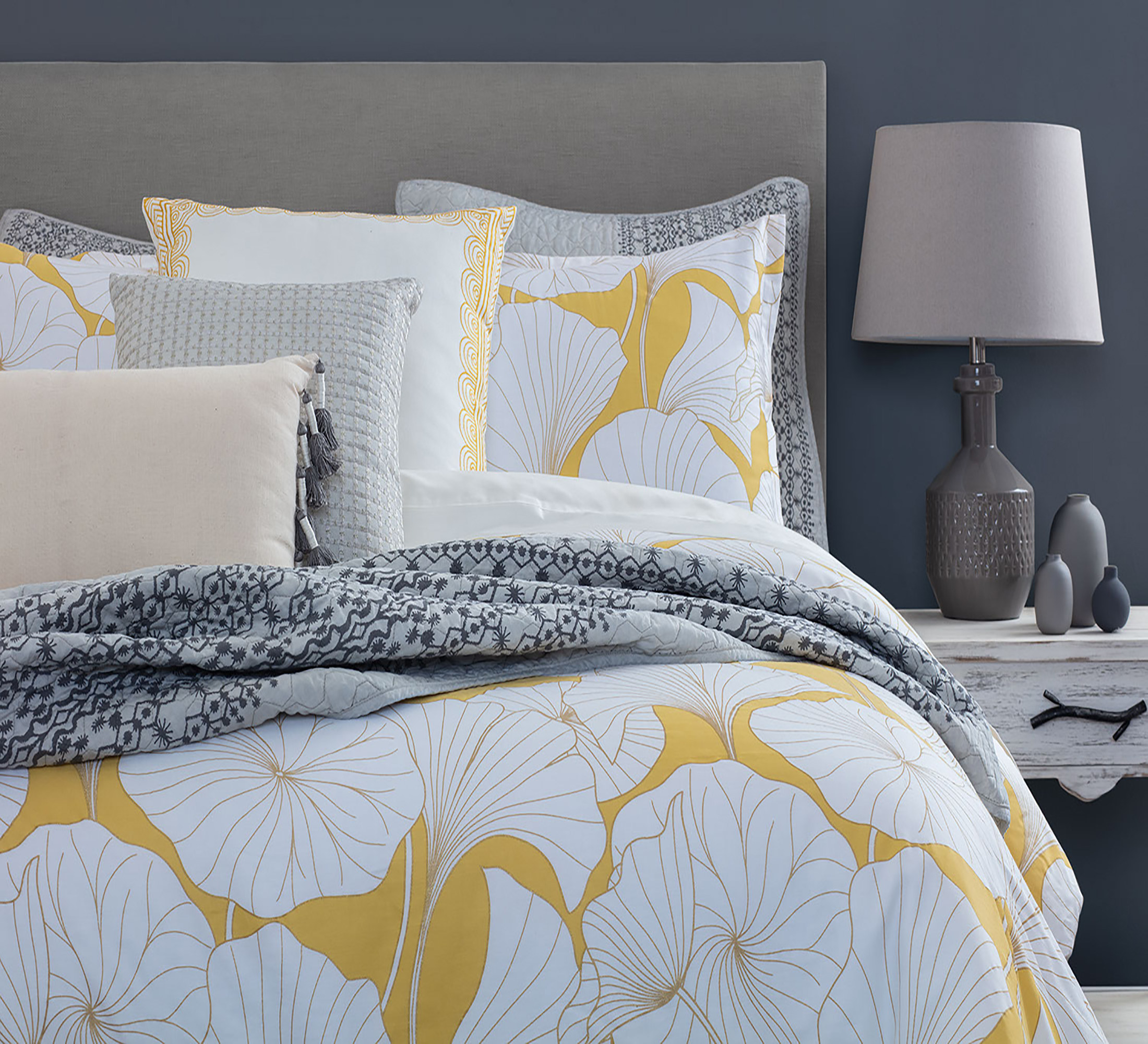 A yellow comforter and shams with a white flower pattern