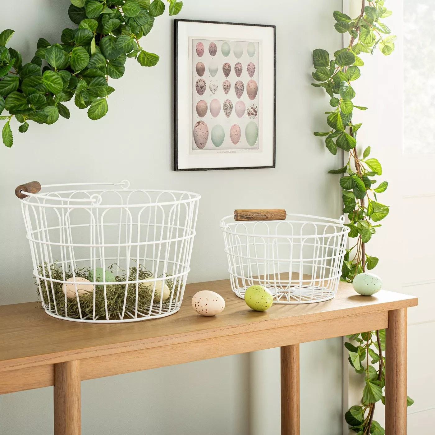 The white wire baskets on a table holding Easter decorations