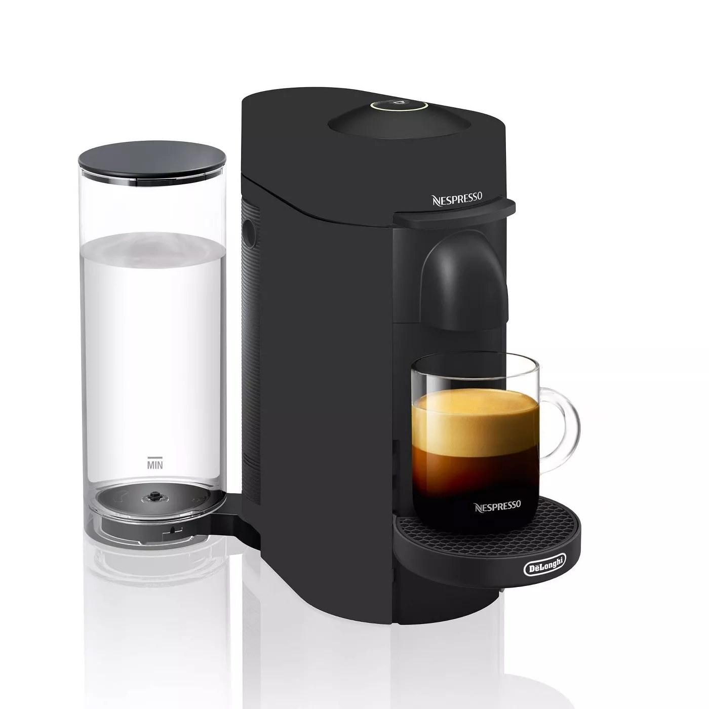 The black Nespresso maker brewing a caffeinated beverage