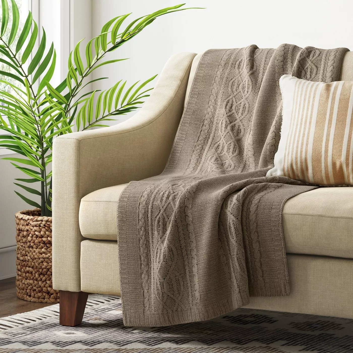 The taupe cable knit throw draped over a couch