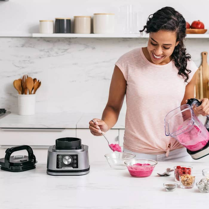 A model using the blender to make smoothies in a kitchen