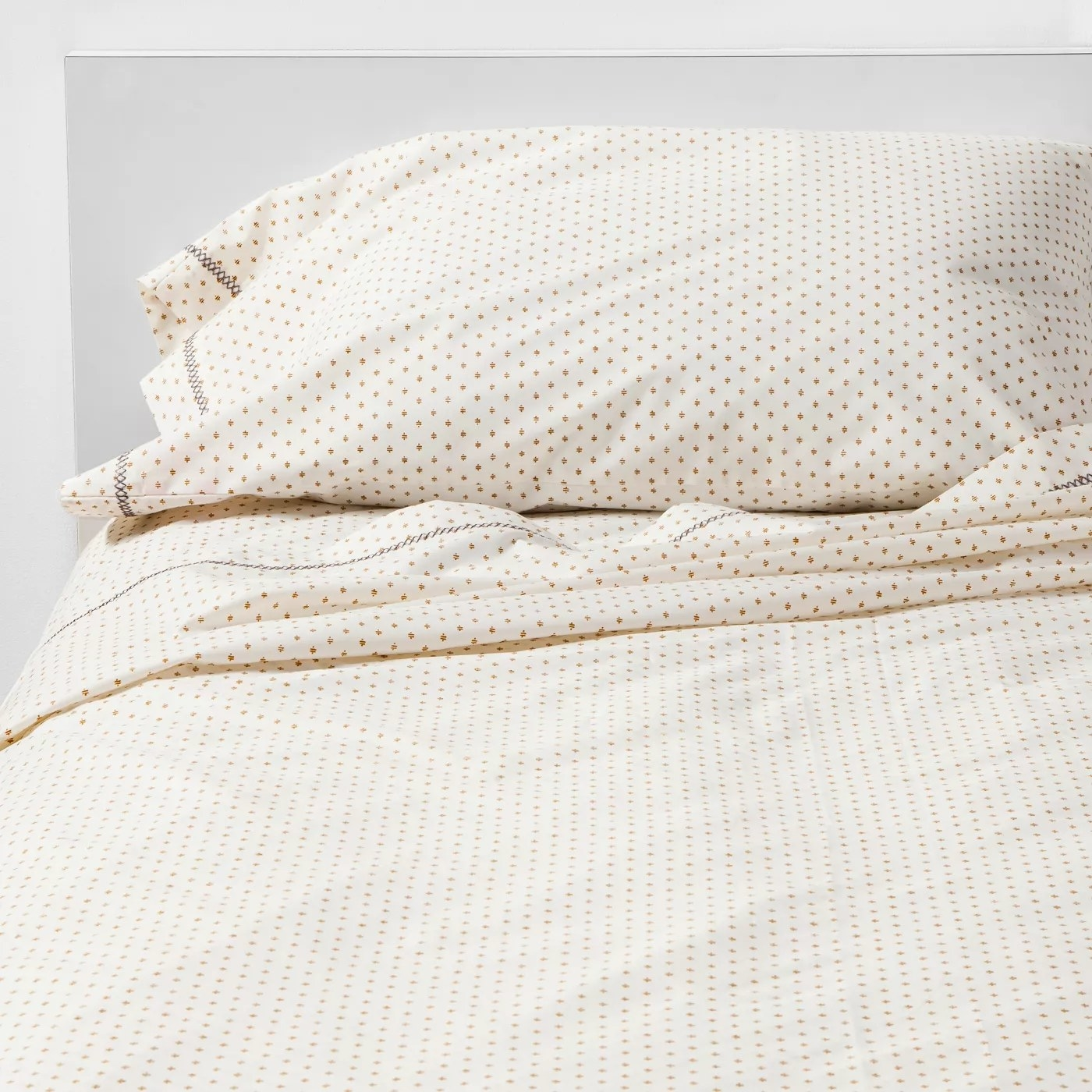 The yellow and white cotton sheets on a bed