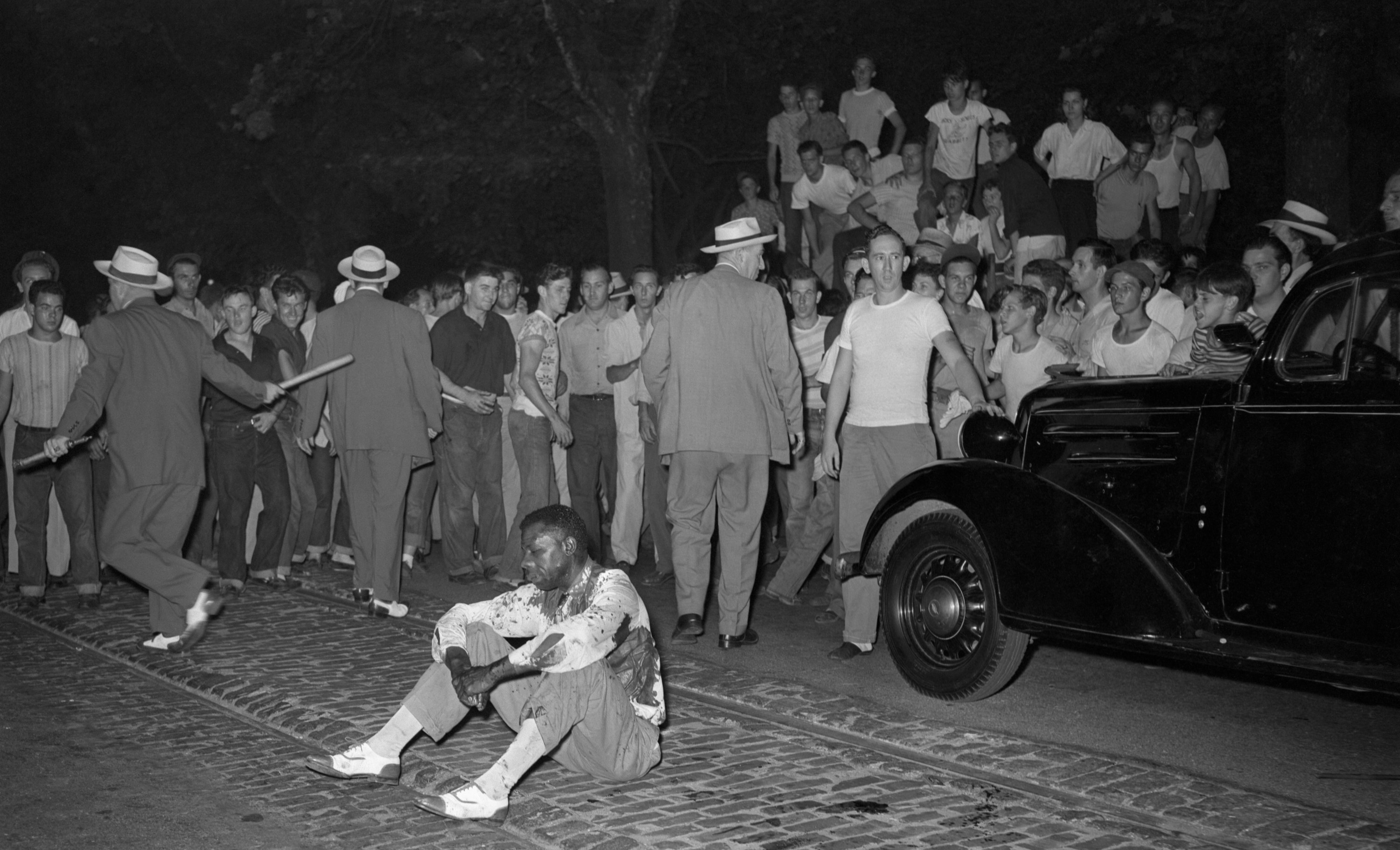 A beaten Black man sits in the street while police check members of the mob who attacked and stoned him during a race riot, which started when Black people were permitted to use public swimming pools along with whites for the first time