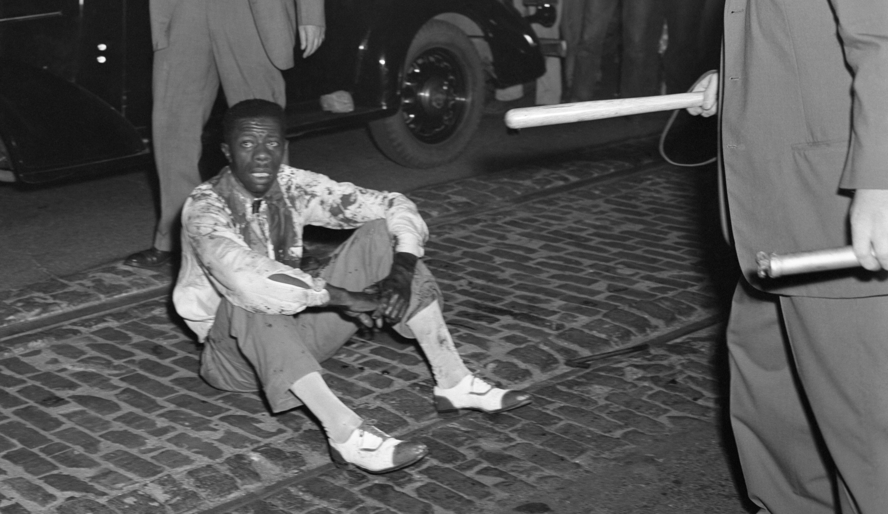 A Black man, whose clothes are soaked with his blood, sits on the street after being beaten and stoned by the mob during the St. Louis race riot