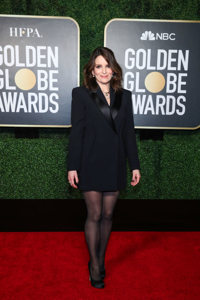 Tina poses in her short tuxedo dress, tights, and high heels