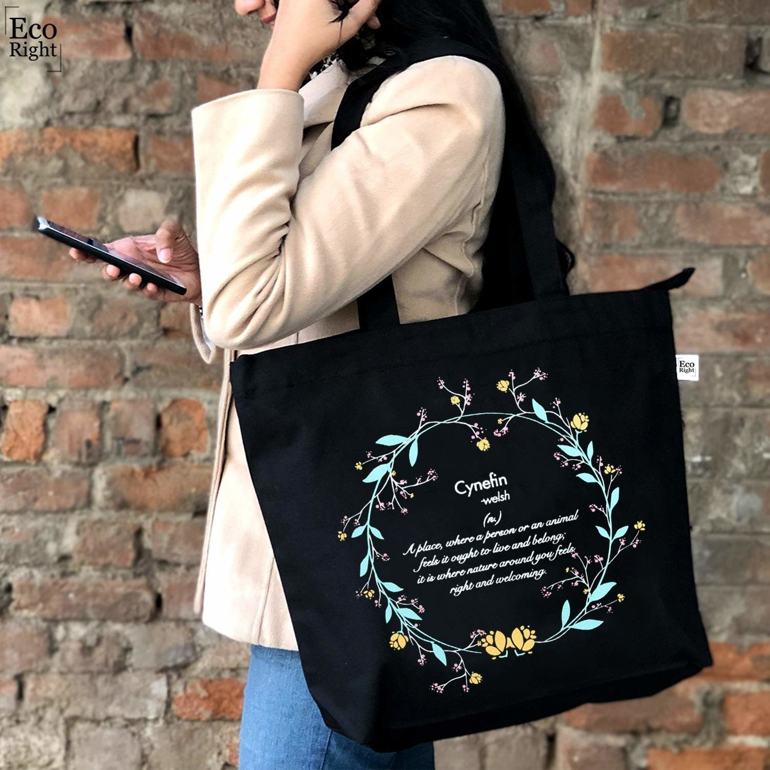 A black tote bag with a floral design and the meaning of 'cynefin' written on it.