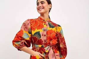 model wearing a super colorful floral dress with button up detailing and a tie waist