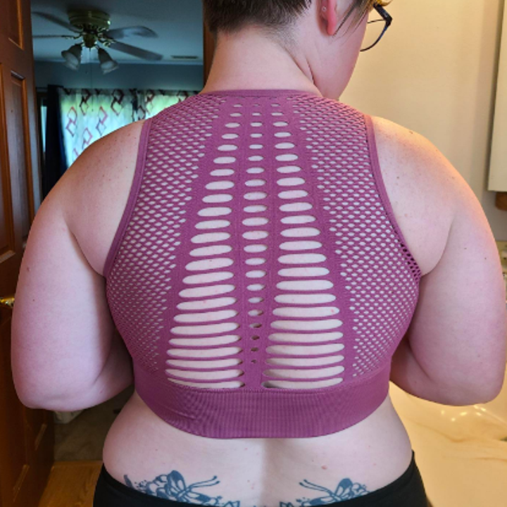 Reviewer showing the mesh and cut design on the back of the bra
