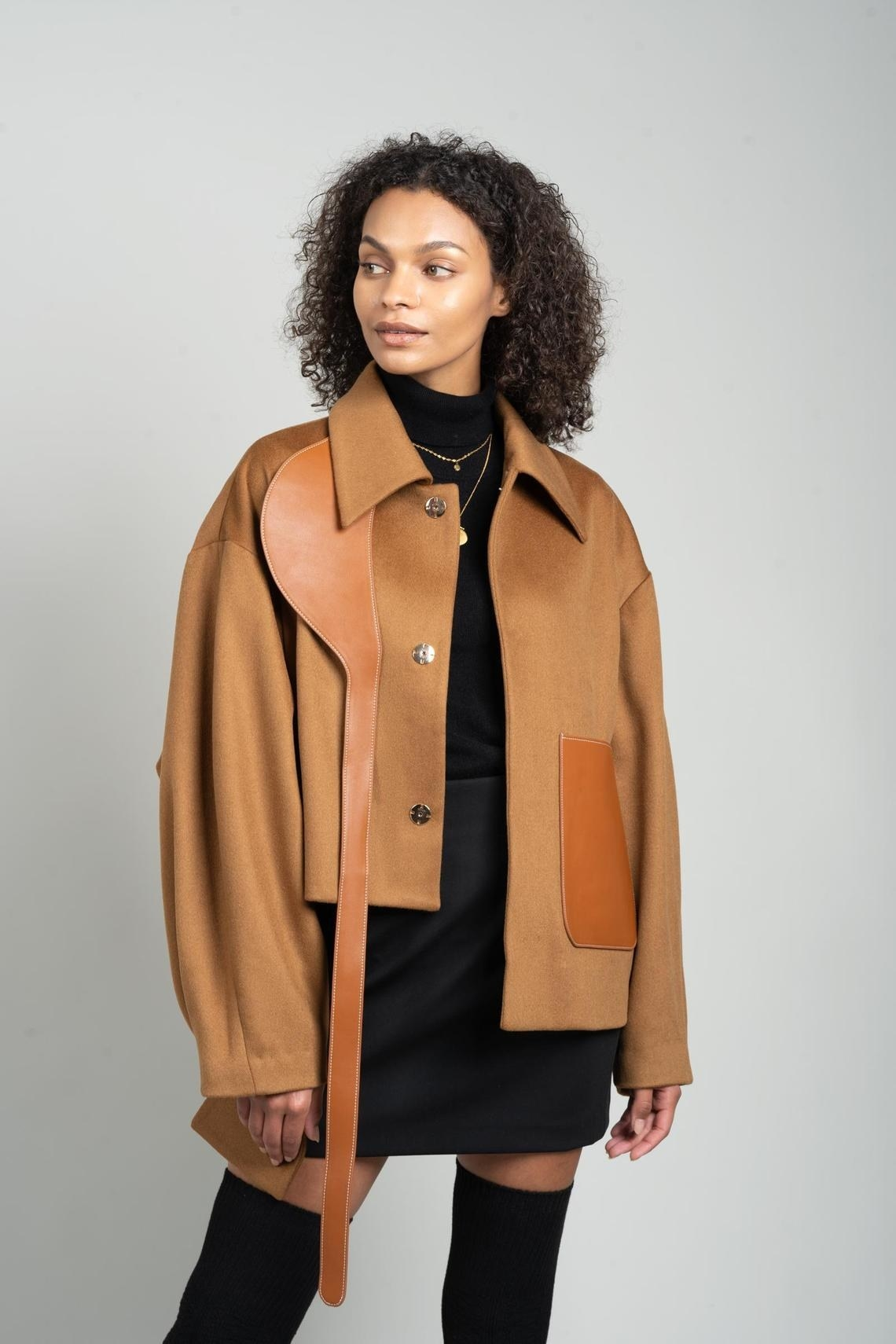 Tan and faux leather jacket with asymmetrical lengths on the front and back (three different lengths in all). It has a leather pocket on the front of one side and a leather decorative strap from the collar down the other side.