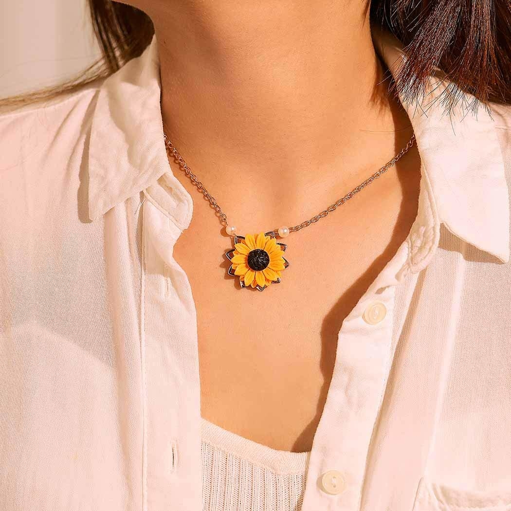 A person wearing the necklace. It has a rose gold chain and a sunflower locket.
