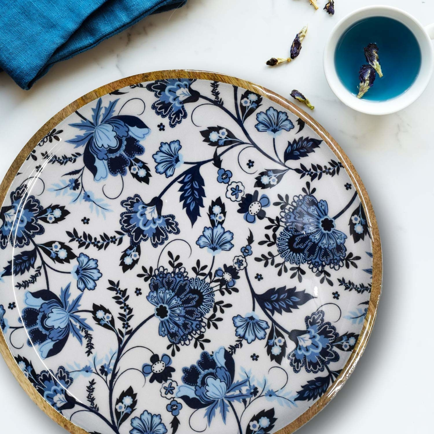 A circular wooden tray with a white and blue floral design.