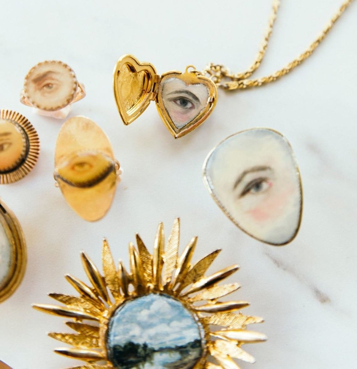 Several tiny gold necklaces, rings, and pendants with painted scenes and eyes