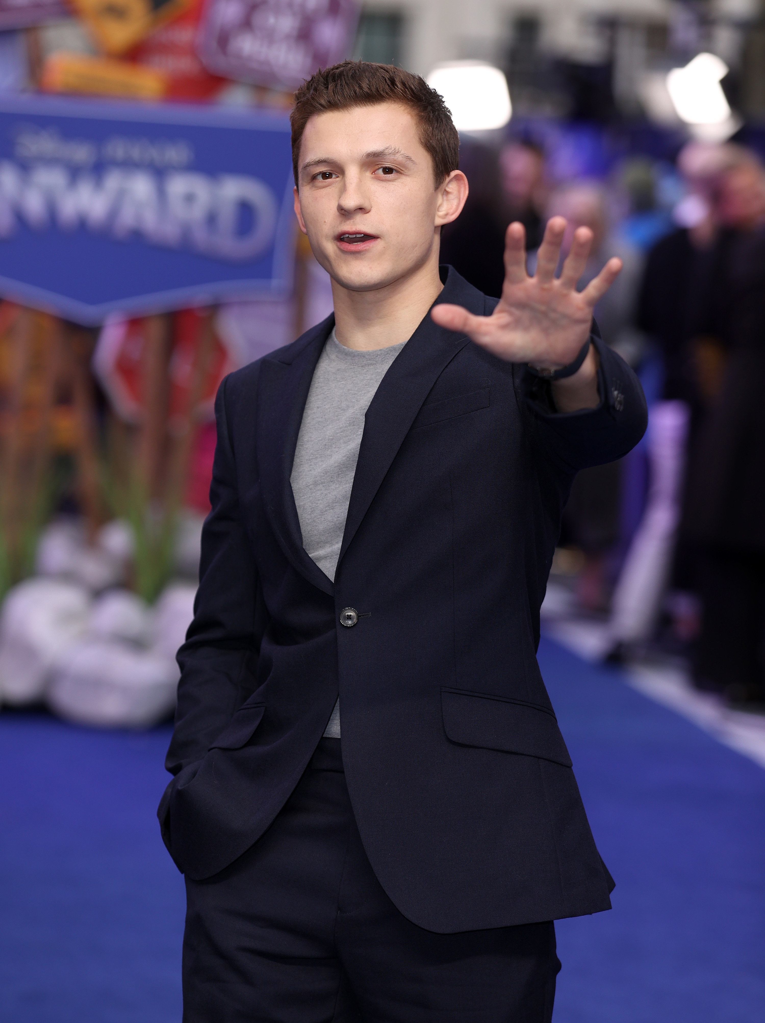 Tom Holland holding his arm up on the red carpet of a premier