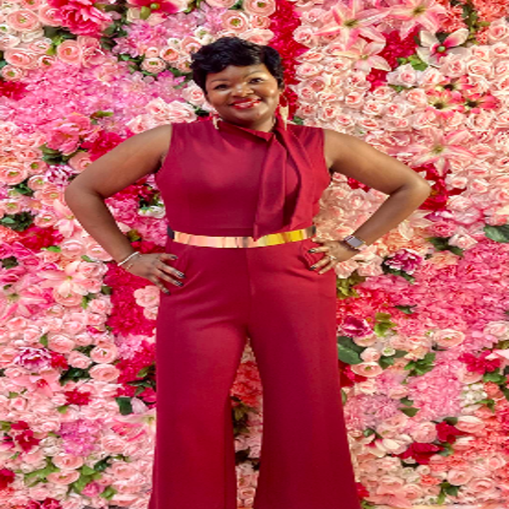Reviewer wearing the flared bottom, sleeveless jumpsuit in red. They've paired it with a gold belt and have the neckline tied off to the side.