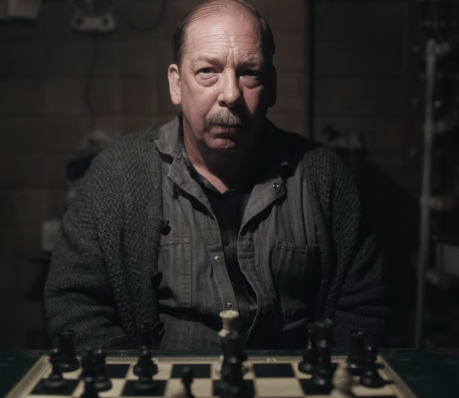 An older man is sitting at a table with a board of Chess in front of him