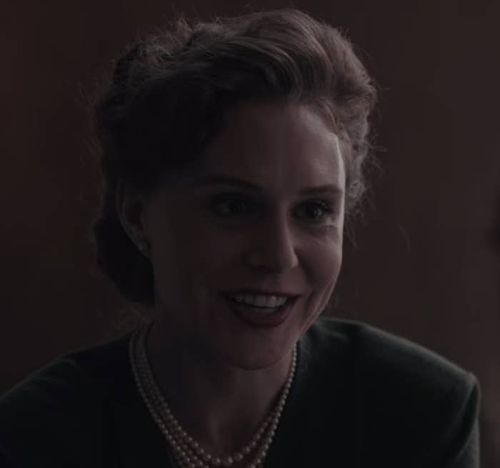 A woman is sitting at a desk, wearing pearls and smiling in a friendly manner