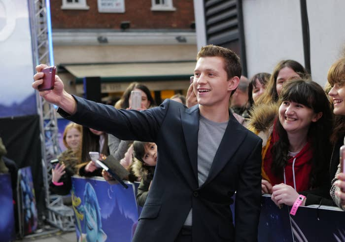 Tom taking a photograph with fans at a premier