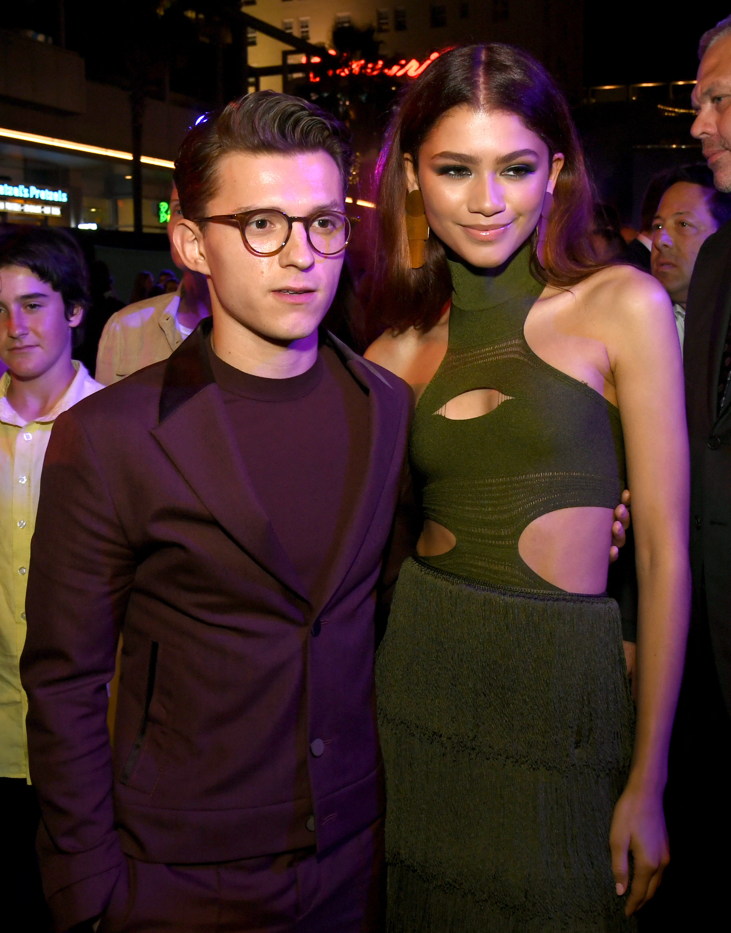 Tom, in a monochrome suit, and Zendaya, in a halter dress with cut-outs, posing together for a photo