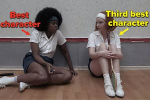 """Two girls are leaning up against a wall while holding a racket as a the one on the left is labeled, """"Best  character"""" and the one on the right is labeled, """"Third best  character"""""""