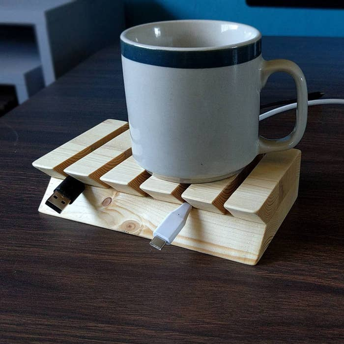 wooden cord organizer propping up phone charger cords