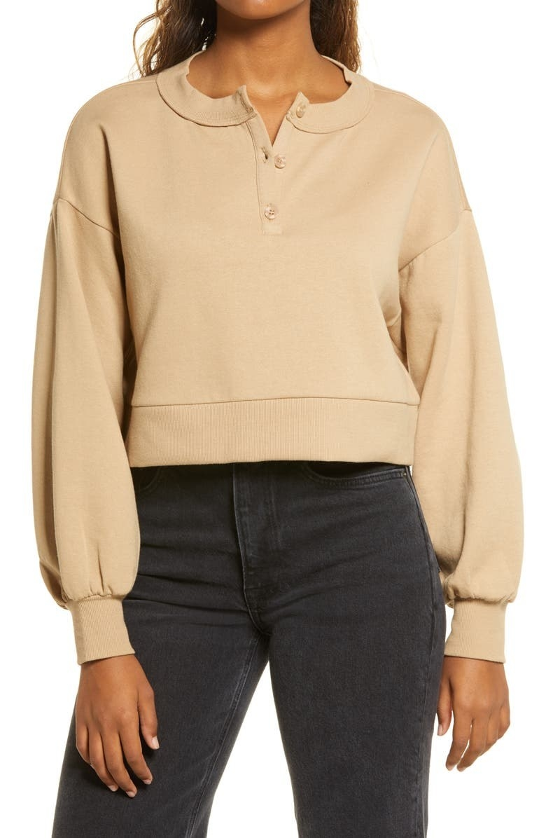 model wearing a beige cropped henley with billowy sleeves