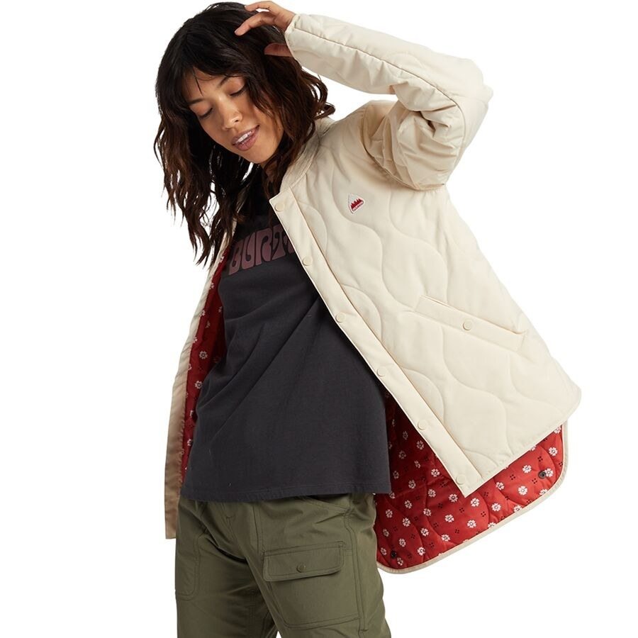 Person wearing lightweight quilted jacket in a cream color. It has red floral fabric inside.