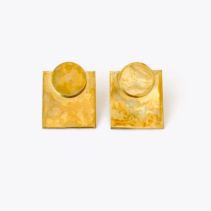 Closeup of earrings. They are squares with a circle plate attached to the tops with a bright gold color and faux aged and hammered details.