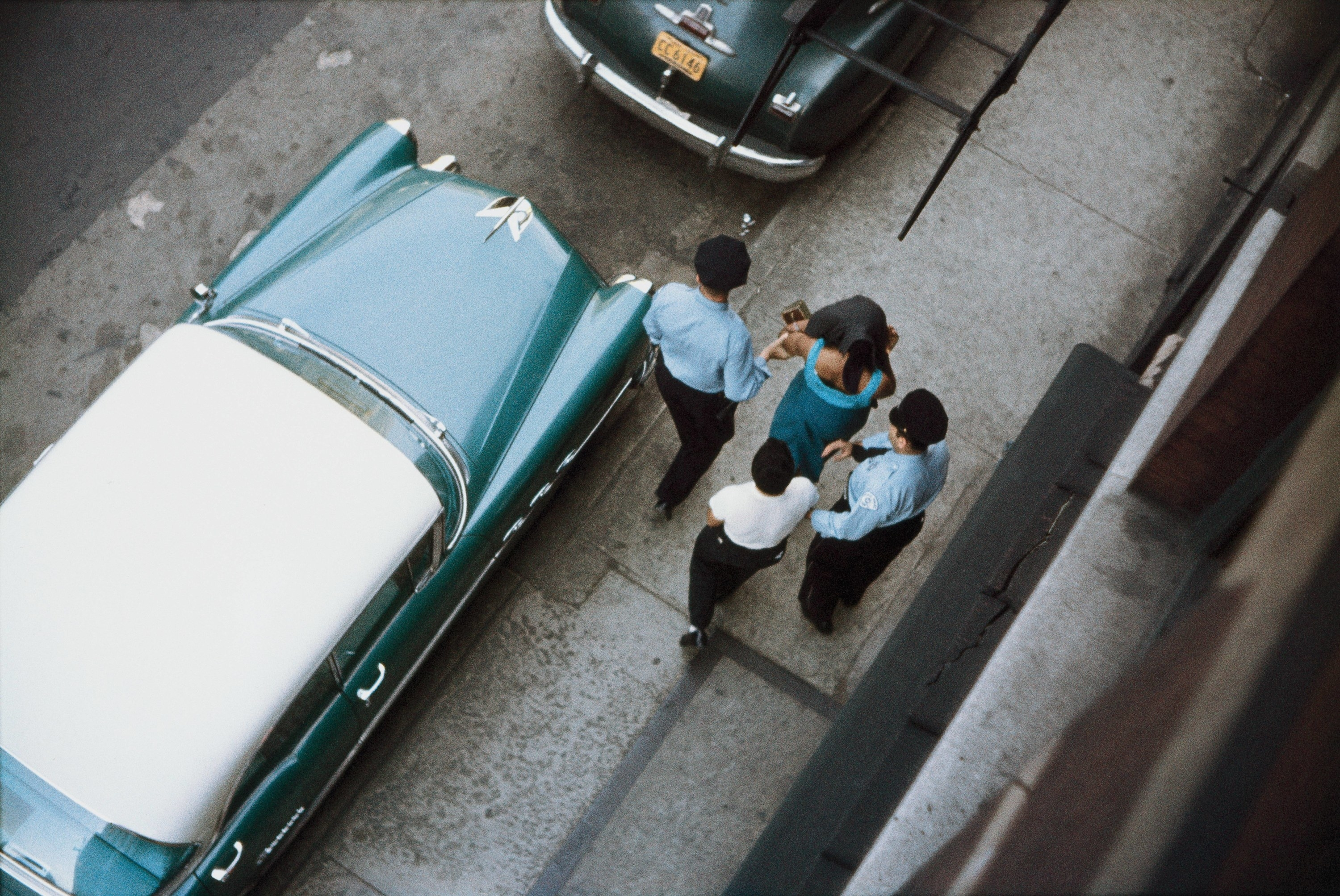 An overhead shot of two policemen leading away a woman down a street with a man behind her