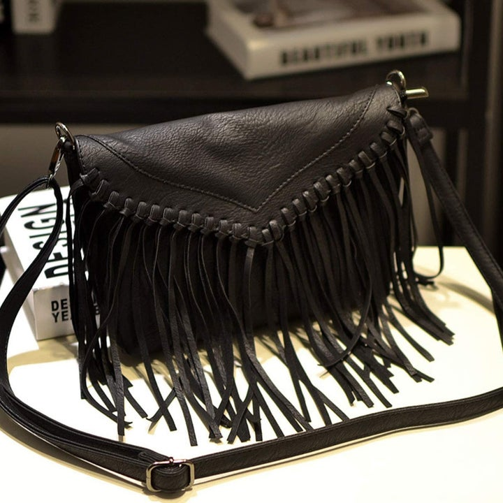 Small crossbody in faux black leather with long fringe on the front