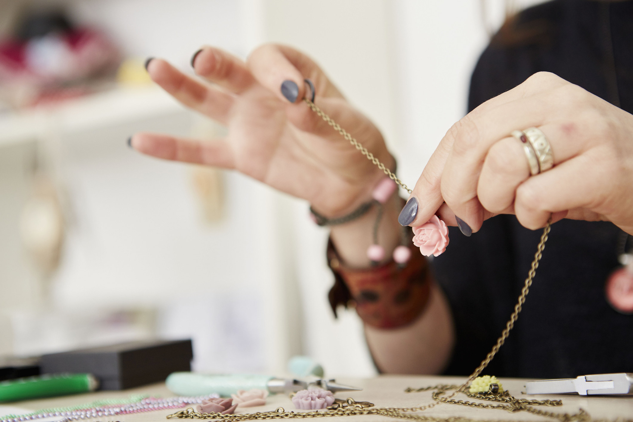 close up of a person making a necklace