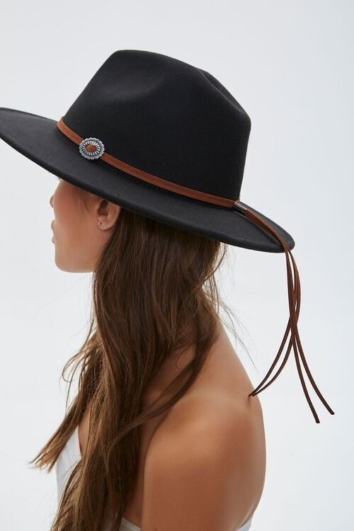 Model wearing cowboy-esque hat with brown faux leather straps wrapped around the base of the hat and hanging from the back