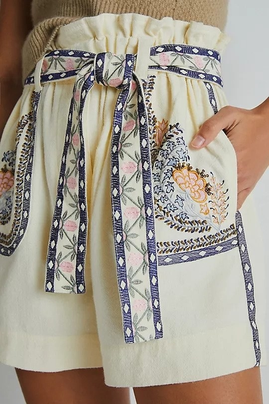 Cream high waisted shorts with pockets and a tie belt, all with embroidered floral details